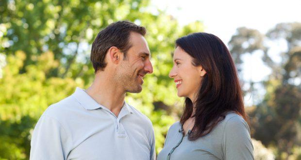 Casal Sorrindo com Árvores ao Fundo