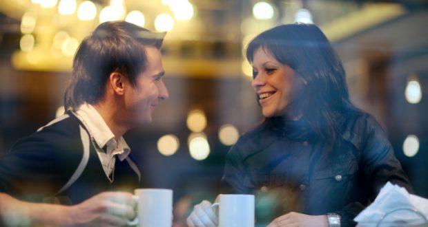 Casal conversando com canecas na mão